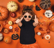 child at Halloween with thumbs up