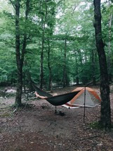 a man in a hammock by a tent