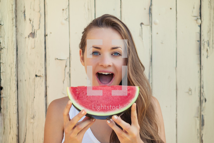 a young woman eating watermelon