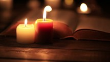 flickering candles and an open Bible