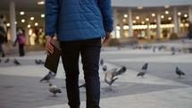 a man walking across a courtyard full of pigeons carrying a Bible