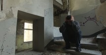 man in an abandoned building with hands over his head