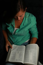 teen girl reading a bible on her lap