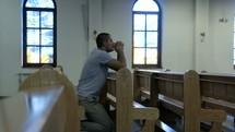 a man kneeling in prayer in a church