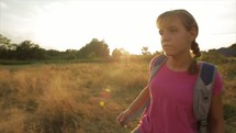 a girl with a backpack walking alone in a field