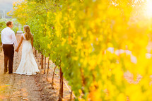Bride and groom outdoors walking thru a vineyard napa valley love romance marriage wedding holding hands man woman