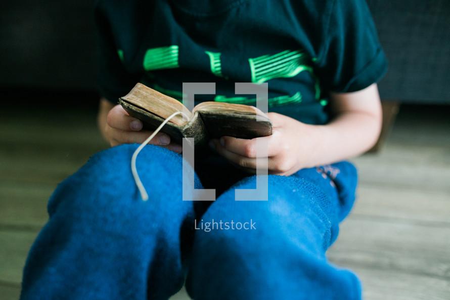 a boy sitting reading a Bible