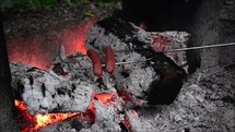 cooking sausages over a campfire
