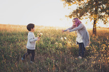 mother and son picking flowers in a field