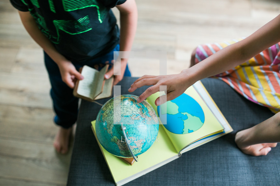 a boy reading a Bible and a girl playing with a globe