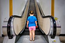 girl child approaching an escalator