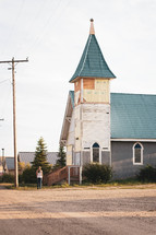 a female standing in front of a church
