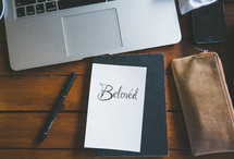 laptop computer, journal, and note with the word Beloved