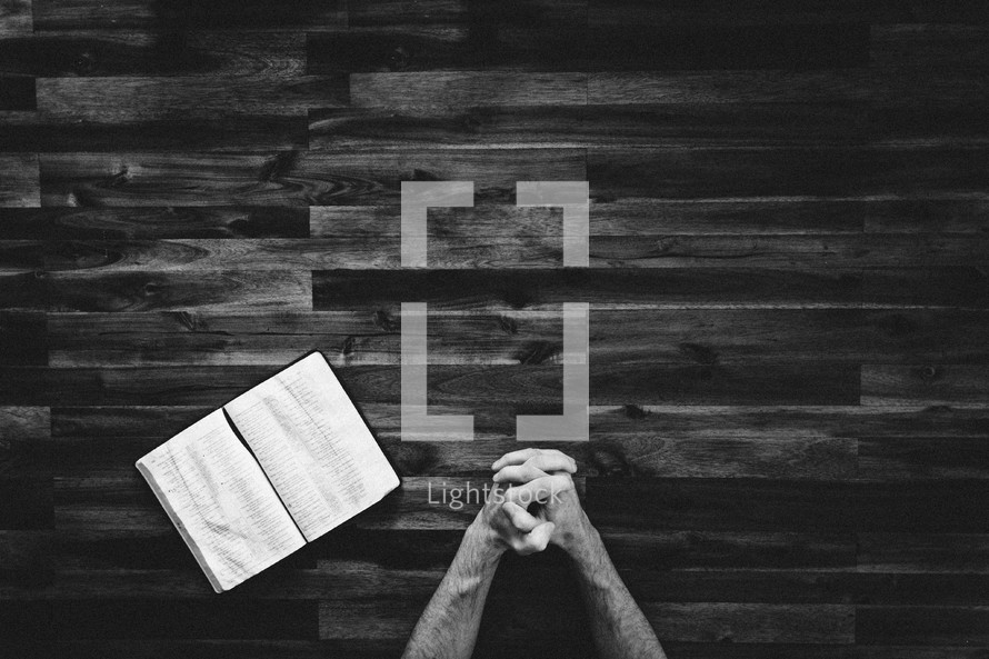 a man with praying hands and an open Bible