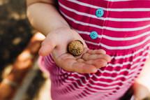 a little girl holding an acorn