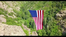 American flag on rope between mountains