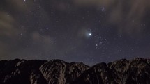 Timelapse of cloud movement and stars over a mountain range.