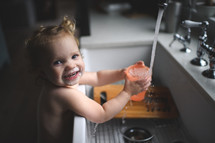 a toddler playing in water at the kitchen sink