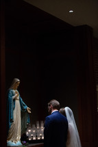 bride and groom praying before a statue of Mary
