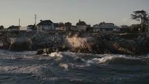 waves crashing into a shore and coastal homes