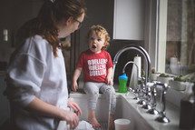 toddler playing in water at the kitchen sink while mom does dishes