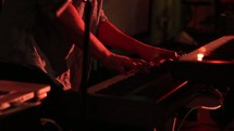 Hands playing a keyboard with a band on stage.