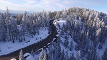 aerial view above a road through a winter forest