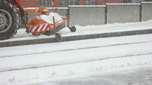 machines clearing snow off of a sidewalk