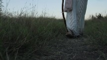 A man in Biblical times walking in a field with his staff.