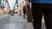 a man carrying a Bible down a city sidewalk