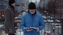 a man standing in a busy city reading a Bible amongst the distractions