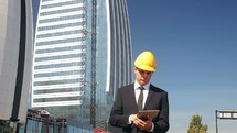 engineer in a hardhat standing in front of a skyscraper