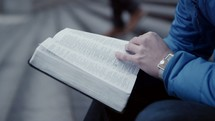 a man sitting on steps in a city reading a Bible
