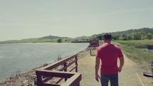 man walking around a lake shore