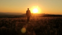 a businessman walking away at sunset