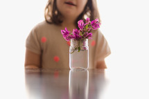 a girl child and flowers in a glass jar
