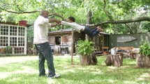 A father swings his young son around and around in the back yard.
