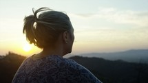 a woman sitting on a mountaintop at sunrise