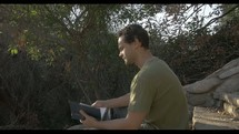 man reading a Bible and praying outdoors