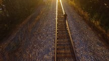 a man walking down railroad tracks under bright sunlight