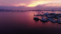 boats in a bay under a purple sunset