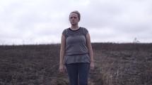 a woman walking through a burnt field