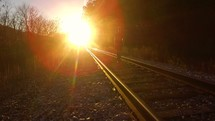 A man walking on train tracks under bright sunlight