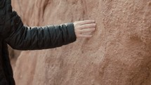 a woman in a coat touching a rock
