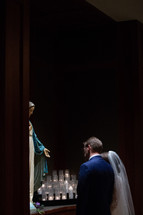 bride and groom praying before Mary statue