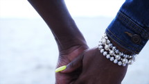 young African American couple holding hands by ocean water wearing jewelry  in a white dress and jeans jacket during an overcast cloudy day cinematic 4k
