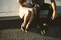 a couple sitting on a sidewalk