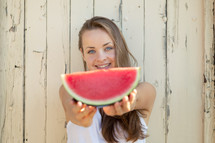 a woman holding a watermelon