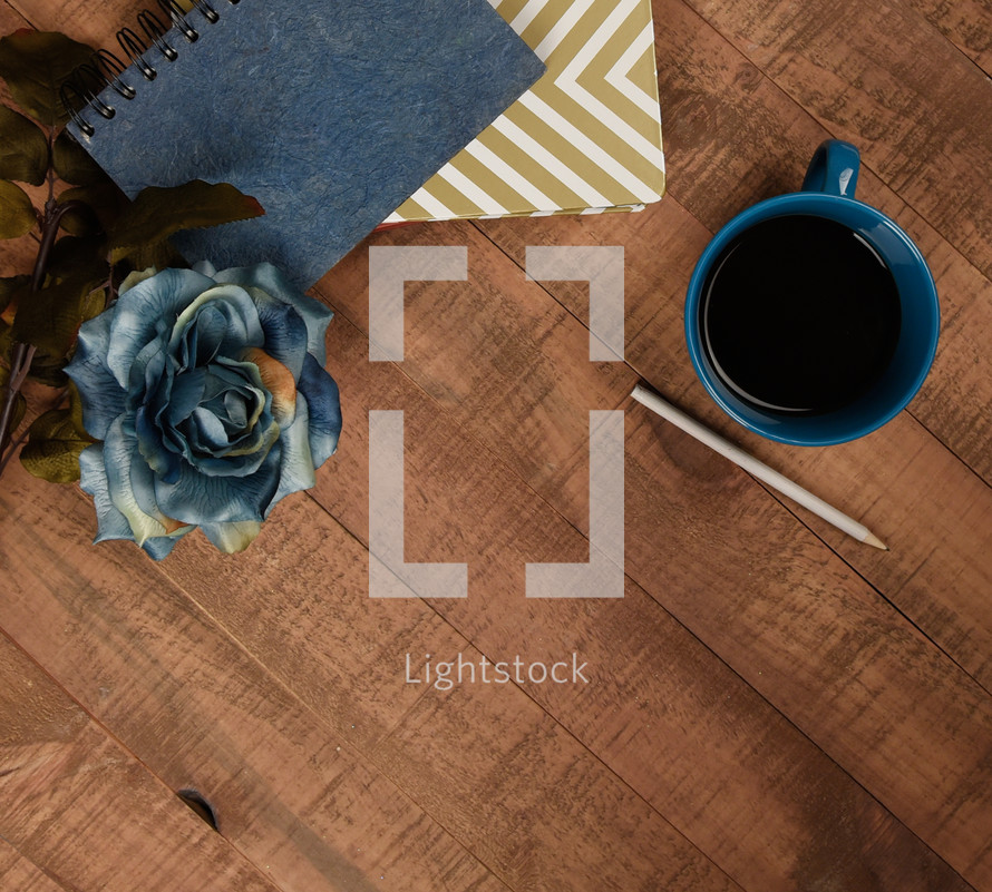 blue rose, coffee mug, pencil, and notebooks on a wood table