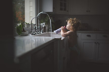 toddler drinking water by a sink